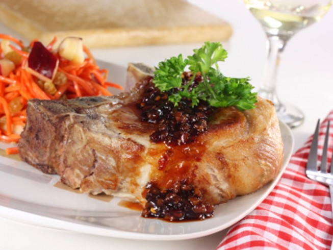 Thick and meaty pork chops are perfectly cooked and topped with a ...